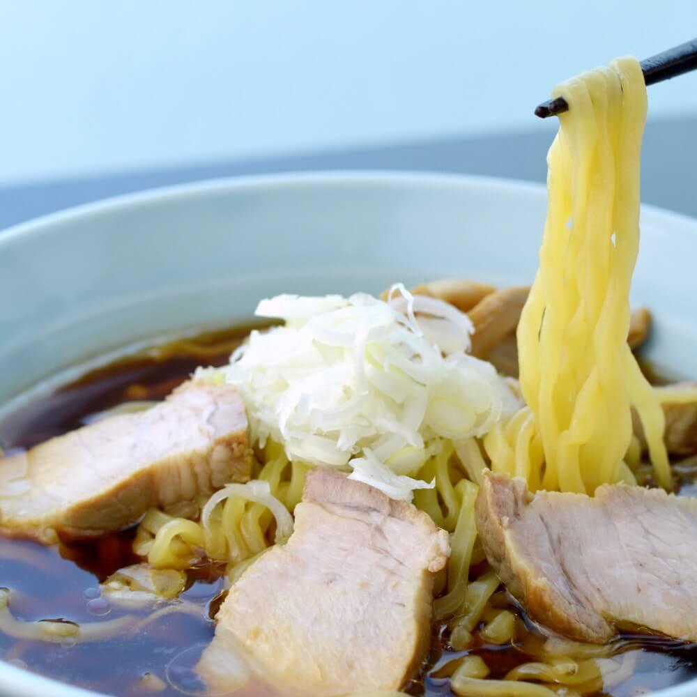 商品名:喜多方、多加水 熟成の平打ち太麺・ちぢれ麺のあっさり醤油ラーメンの麺持ち上げ