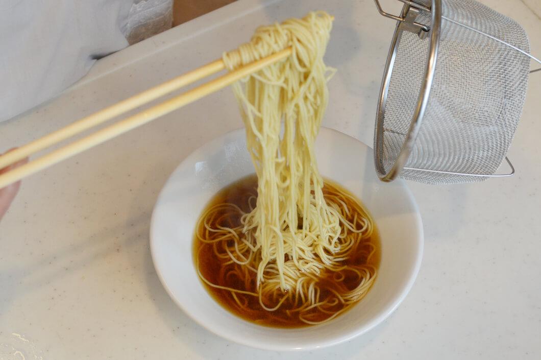 スープに浸した麺をまっすぐ持ち上げて麺を整える