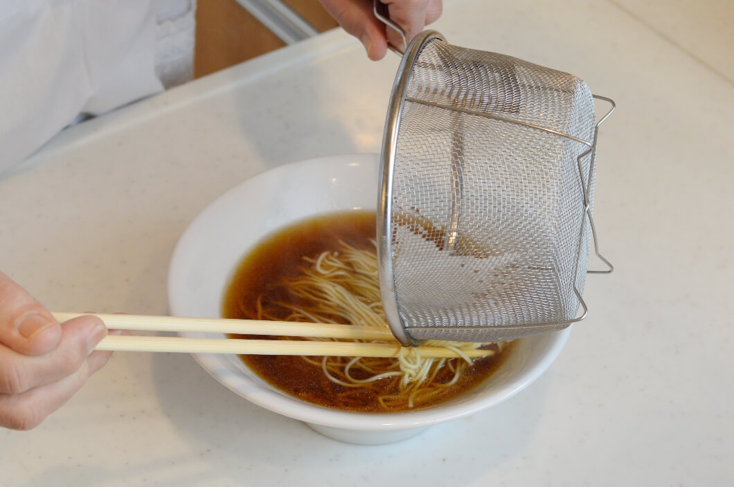 麺と折りたたむようにして整えたらザルのフチでどんぶりに滑り入れる