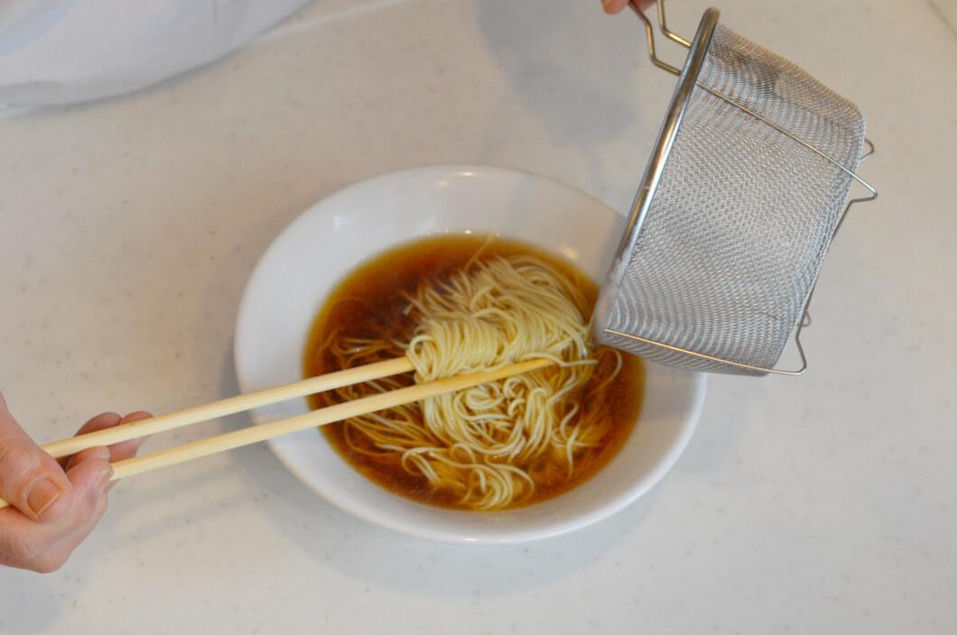 どんぶりに入ったスープにザルから出した麺をひたす