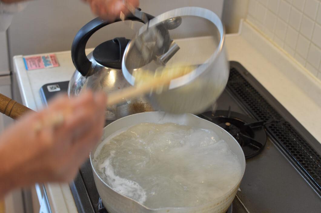 ラーメンの麺を鍋からとりあげ湯切りする